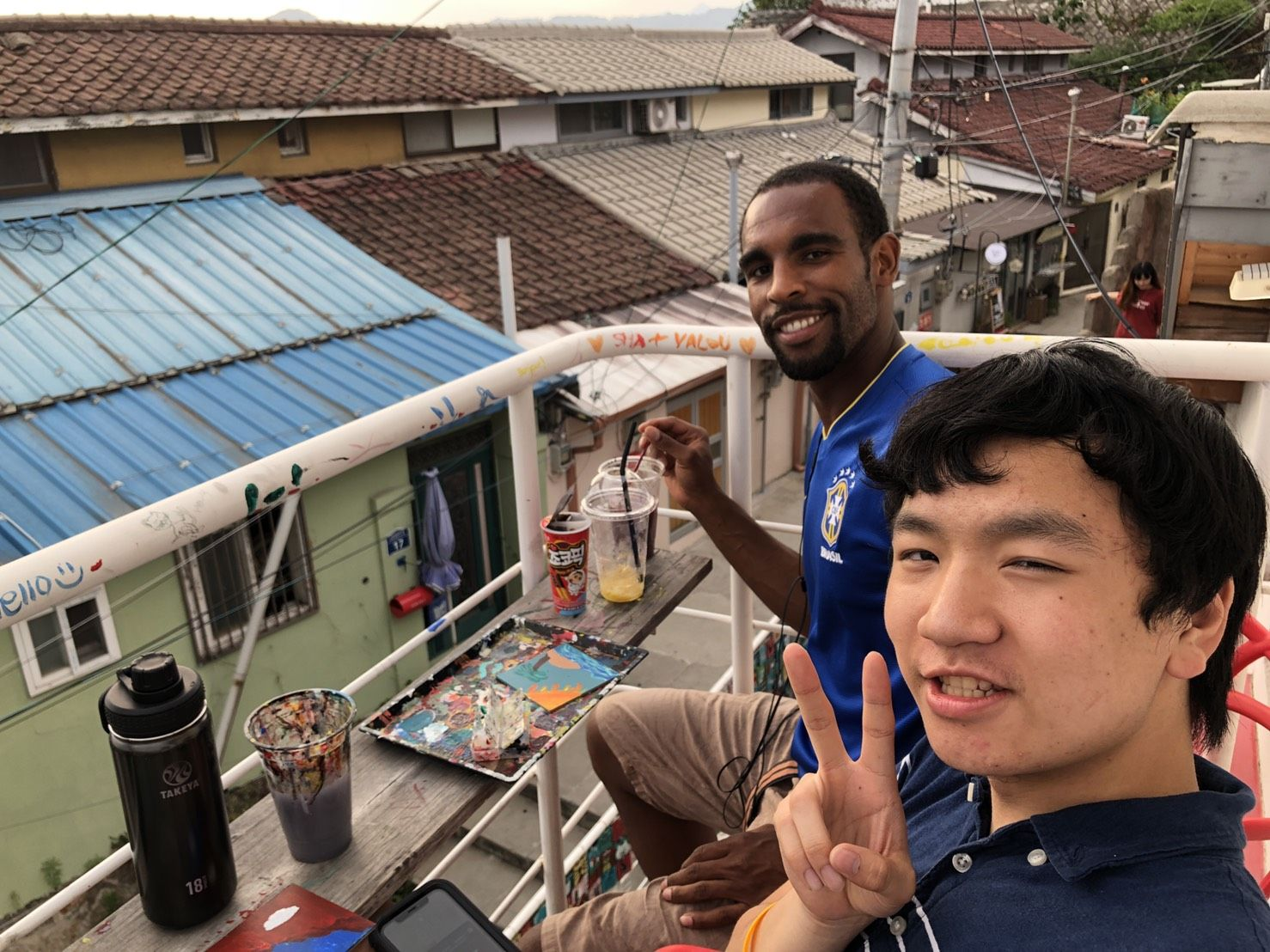 Student and program leader sitting on the rooftop of a cafe in Iwha Mural Village.